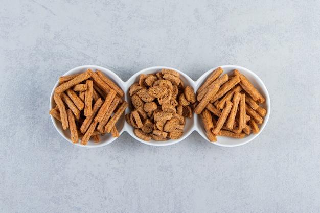 White bowls of tasty crunchy crackers on stone background.