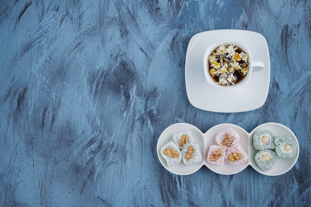 White bowls of various sweet delights with nuts and tea on blue surface.