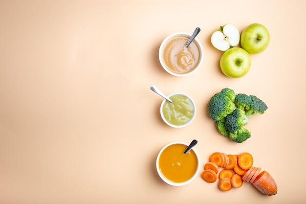 텍스트를 위한 공간이 있는 파스텔 배경에 건강한 천연 이유식을 곁들인 흰색 그릇. 신선한 과일과 야채 퓌레, 플레이레이, 꼭대기 전망, 개념. 당근, 브로콜리, 사과로 만든 어린이 식품