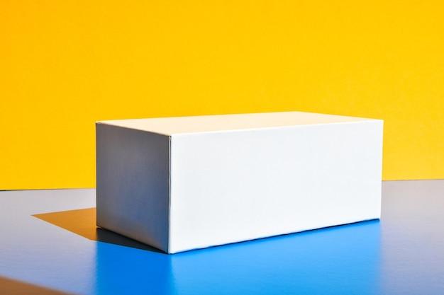 흰색 상자입니다. 마약 상자 모형. 모형. 공간을 복사합니다. 노란색과 파란색 창의적인 미니멀리즘 아이소메트릭 배경입니다. 단단한 빛. 그림자
