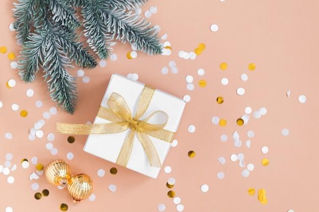 紙吹雪ゴールドカラーボールとモミとベージュの背景にクリスマスプレゼントの白い箱
