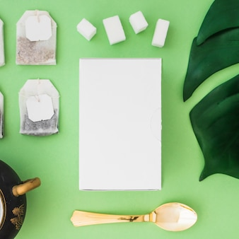 Scatola bianca, cubetti di zucchero e bustina di tè su sfondo verde