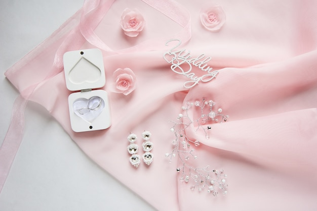 White box for wedding rings on pink chiffon with wedding accessory