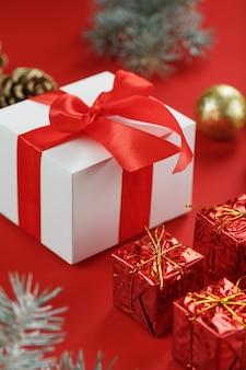 Белая коробка с подарком и красным бантом, вокруг елочные игрушки с еловыми ветками на красной стене. вид сверху