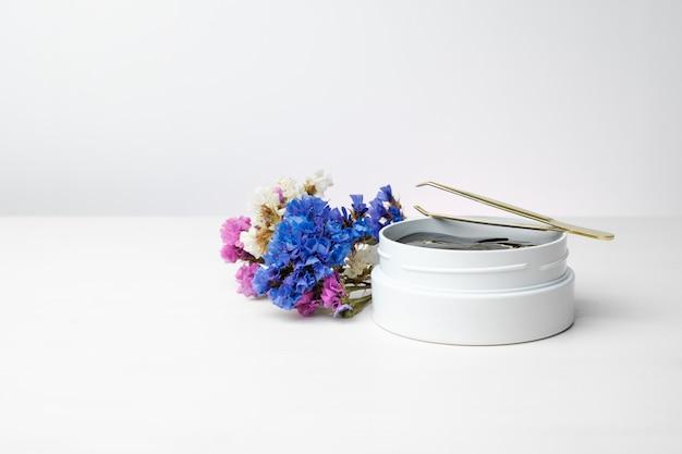 Белая коробка с золотыми пятнами и пинцетом на белом столе с яркими цветами