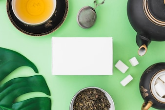 White box with herbal tea and sugar cubes on green backdrop
