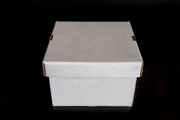 White box with a lid isolated on a black space. template for design, layout.