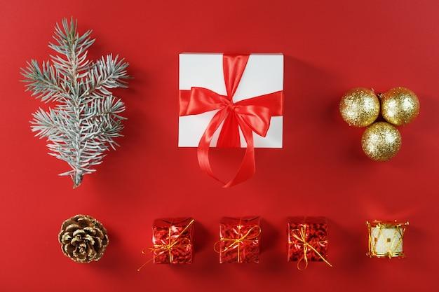 Белая коробка с падарком и красным бантом вокруг елочных игрушек с еловыми ветками