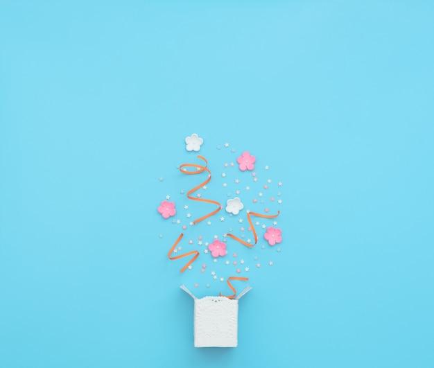 パーティーの紙吹雪、ストリーマー、花が青で爆発する白いボックス。