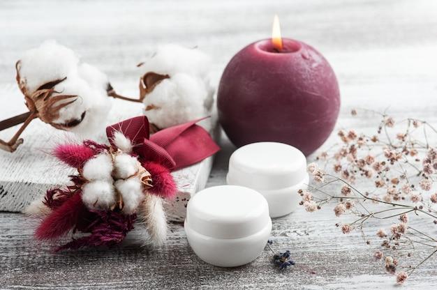 Белые коробки крема, зажженная свеча и букет сухих цветов марсала. композиция спа на деревянном столе