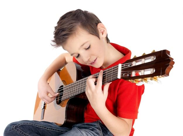 白人の少年は白で隔離のアコースティックギターで遊んでいます