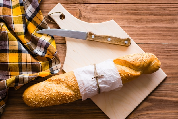 White bread or baguette and knife on cutting board. top view
