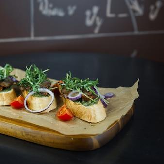 Arugula와 붉은 양파 링과 레스토랑에서 나무 보드에 붉은 신선한 토마토 조각 고기 페이트와 흰 빵 샌드위치. 맛있는 음식과 건강한 저녁 식사