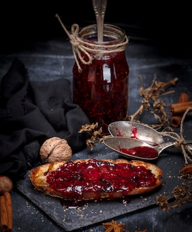 White bread toast spread with raspberry jam