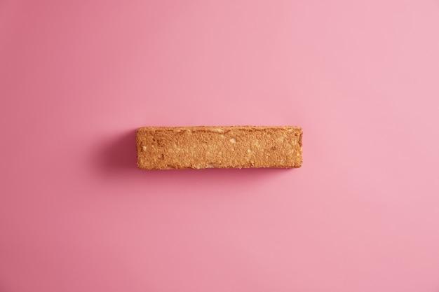 バラ色の背景の上に分離された、上から撮影された食欲をそそるクラストと白パンのトースト。穀物パンのスライス。おいしいおいしい朝食。おやつと食べ物。適切な実質的な栄養の概念
