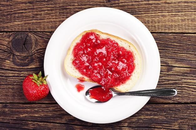 나무 테이블에 딸기 잼이 있는 흰 빵. 평면도