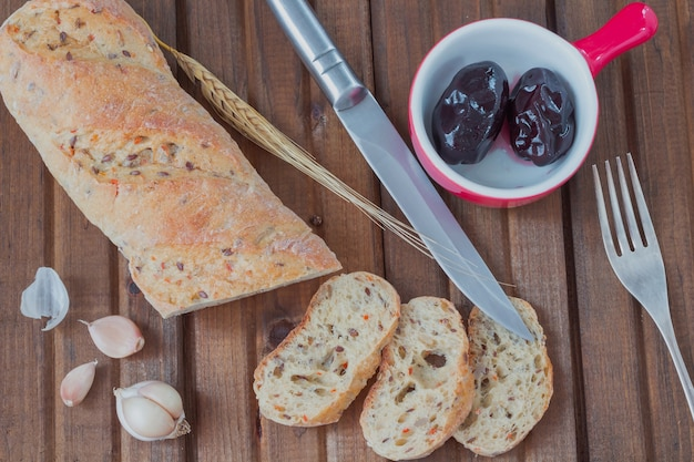 White bread with sunflower seeds sliced into pieces. pickled plums in a ceramic dish. knife. fork. garlic and twig barley