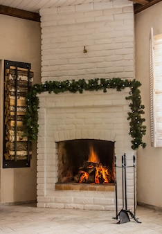 White brick fireplace decorated with a garland for christmas