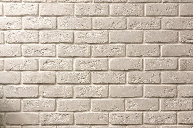 White brick textured wall with a slight yellow tint