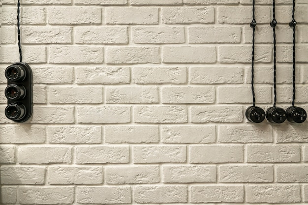 White brick textured wall, with sockets, switches and electrical wiring. loft wall
