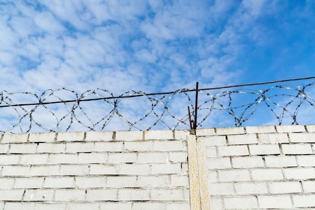 Белая кирпичная стена и колючая проволока