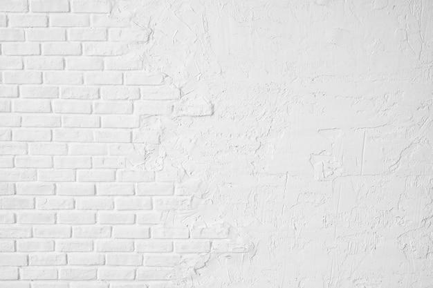 白いレンガの壁の半分は漆喰で覆われています。コピースペースのテクスチャの白い背景。 Premium写真