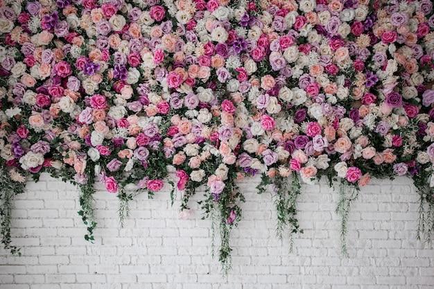 Белая кирпичная стена с красивыми цветами в комнате