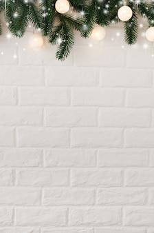 White brick wall with fir branches and christmas lights in the form of white balls.