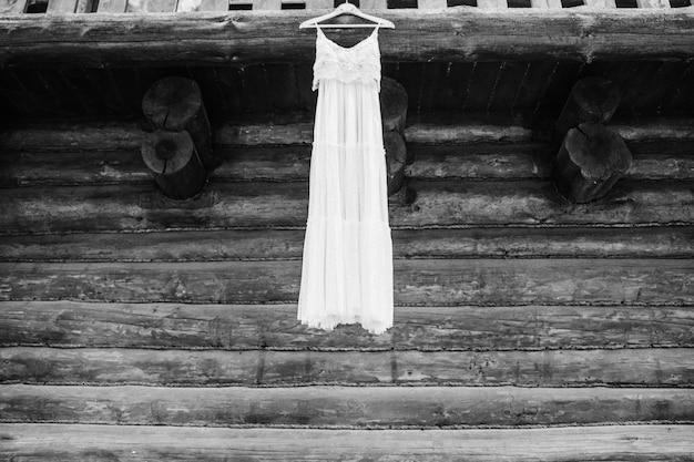 오래 된 나무 벽 근처 흰색 신부 드레스