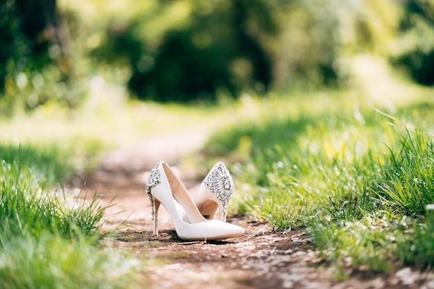 森の小道に立つラインストーンで飾られた白いブライダルシューズ