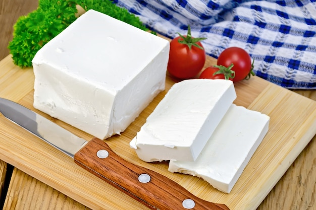 白いブラインチーズ、ナイフ、パセリ、トマト、木の板の背景にナプキン