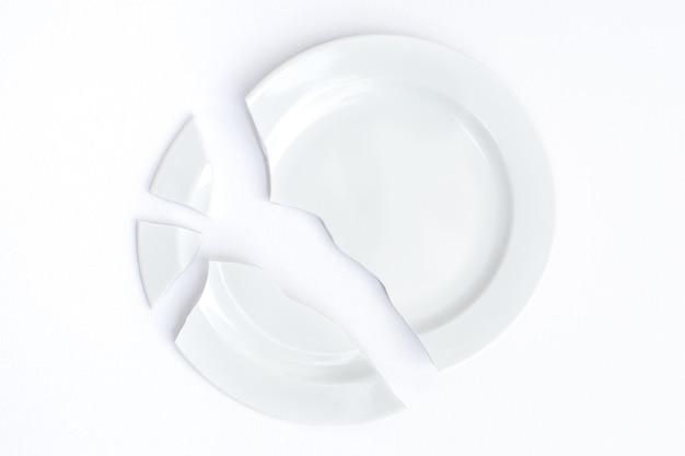 Белая сломанная тарелка на белом фоне. понятие разрушения, разлада.