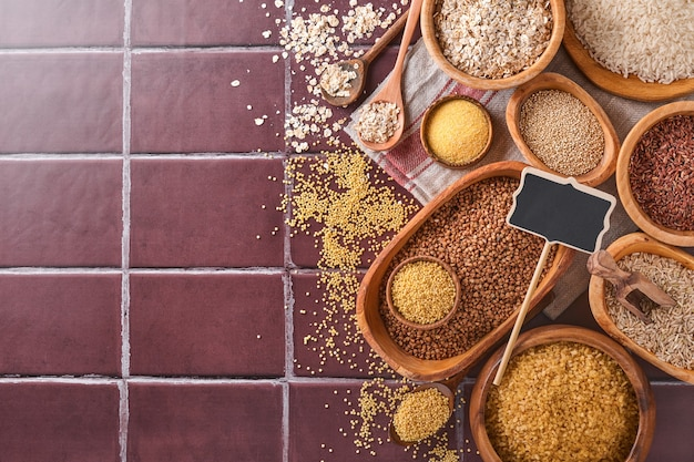 白、茶色、赤米、そば、キビ、とうもろこし割り、キノア、ブルガーを茶色の石の台所のテーブルに置いた木製のボウルに入れます。グルテンフリーのシリアル。コピースペースのある上面図