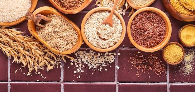 밝은 회색 식탁에 있는 나무 그릇에 흰색, 현미, 붉은 쌀, 메밀, 기장, 옥수수 가루, 퀴노아, 불거. 글루텐 프리 시리얼. copyspace와 상위 뷰입니다. 배너.