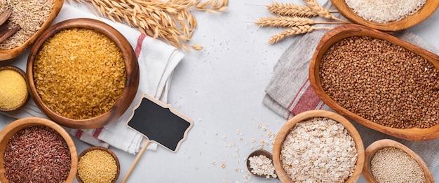 白、茶、赤米、そば、キビ、とうもろこし割り、キノア、ブルガーをライトグレーのキッチンテーブルの木製ボウルに入れます。グルテンフリーのシリアル。コピースペース付きの上面図