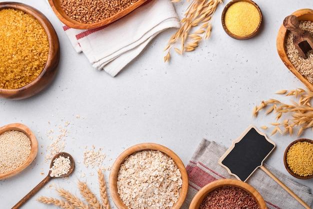 白、茶、赤米、そば、キビ、とうもろこし割り、キノア、ブルガーをライトグレーのキッチンテーブルの木製ボウルに入れます。グルテンフリーのシリアル。コピースペースのある上面図