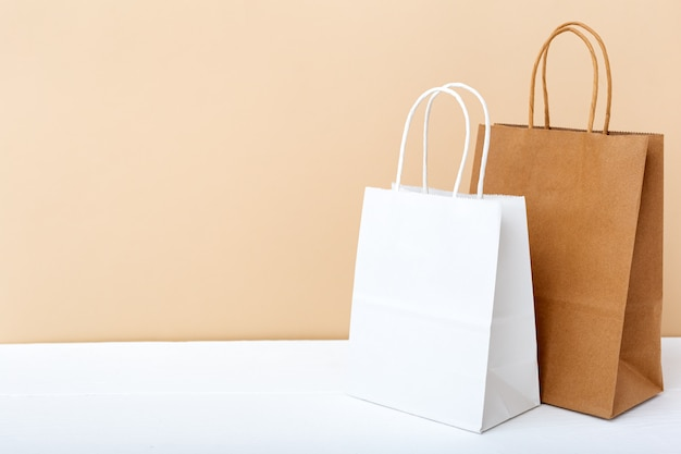 White brown craft paper bags. shopping mockup bags packages on white table beige light background with copy space.