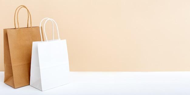 흰색 갈색 공예 종이 봉지. 흰색 테이블 베이지 색 밝은 배경에 쇼핑 모형 가방 종이 패키지