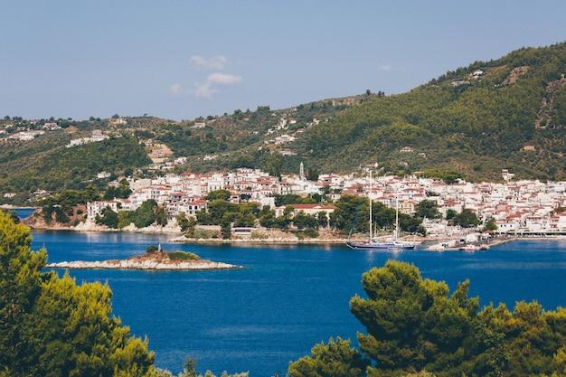 Le case bianche e marroni si avvicinano all'oceano blu circondato dalle montagne con gli alberi a skiathos, grecia