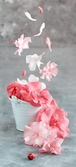 灰色のテーブルにピンクの花でいっぱいの白いバケツをクローズアップ