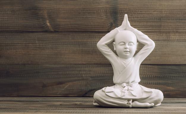 白い仏。木製の背景に僧侶の彫刻。瞑想とリラックス