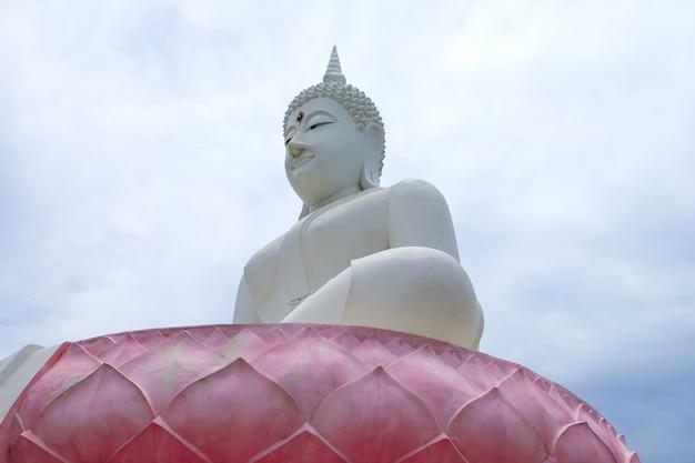 The white buddha status on dim cloud sky background. giant buddha image in thailand