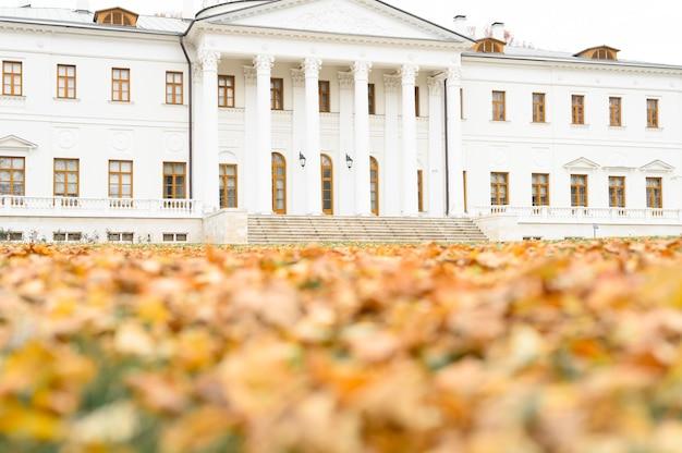 Белое здание поместья и размытые осенние опавшие листья клена на земле в осеннем парке