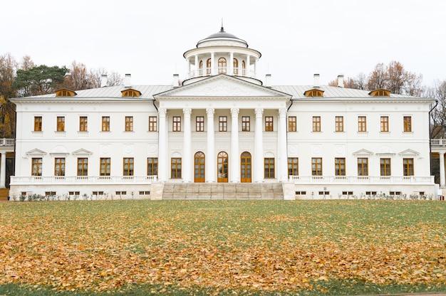 Белое здание усадьбы с колоннами и осенними опавшими листьями клена на земле в осеннем парке