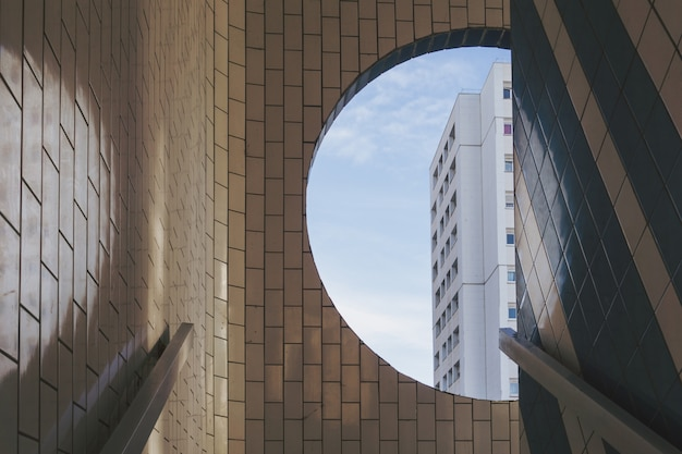 White building visible from the round window in a tiled building