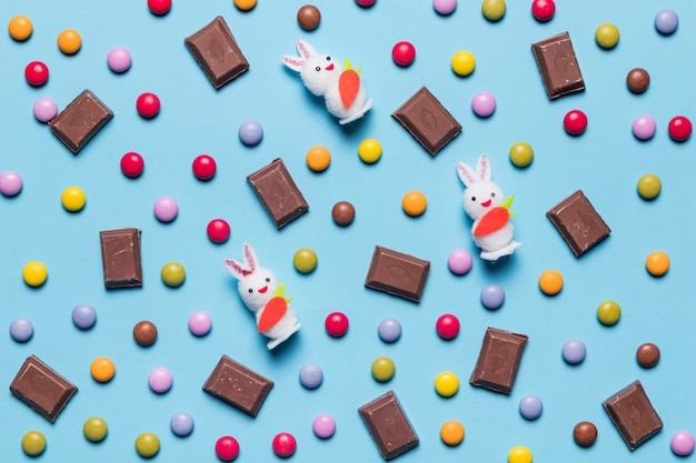 White bunnies; gem candies and chocolate pieces on blue backdrop