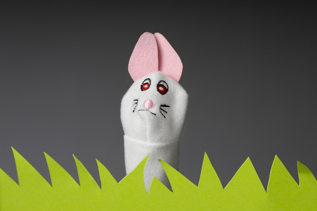 White bunny puppet in paper grass