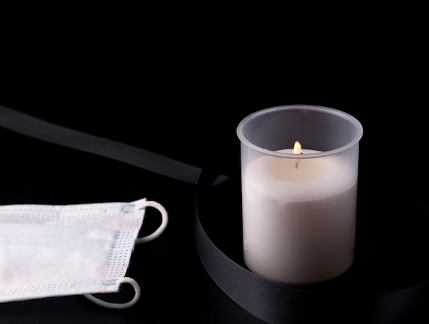 White burning candle next to a black mourning ribbon and a protective medical mask