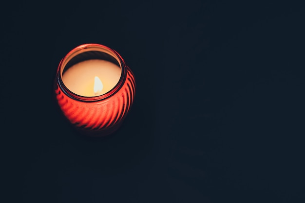 White burning candle in red glass on black background.