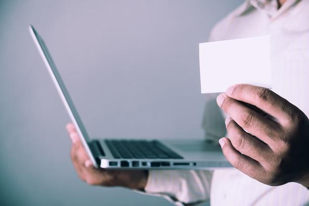 Белая визитная карточка. взрослый бизнесмен работает современный ноутбук размытый фон.